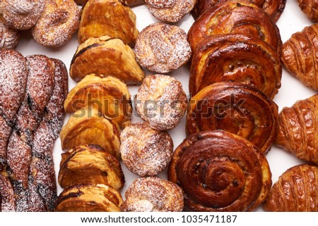 Assortment of french pastries. Delicious buttery croissants close-up. Fresh puff pastry baked croissant, buns on bakery table  #1035471187