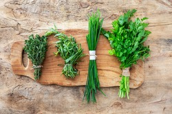 Assortment of fresh aromatic herbs from above on old wood background. Parsley, Mint, Thyme, Basil, Oregano, Rosemary, Chives and estragon.Flat lay.Top view