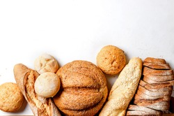 Assortment of fresh baked bread with wheat heads on white table, low key photo, concept healthy or homemade food, for Bakery