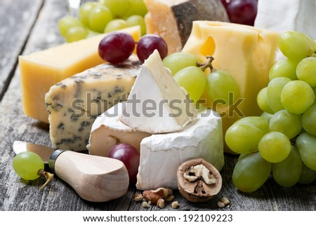 assortment of fresh cheeses and grapes on a wooden background, close-up