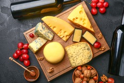 Assortment of fresh cheeses with wine on dark background