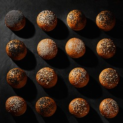 Assortment of fresh, delicious baked buns with black and white sesame and sunflower seeds against black background with copy space. Close-up