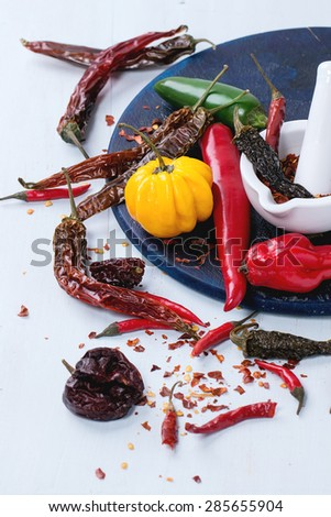 Assortment of fresh, dryed and flakes hot chili peppers with white ceramic mortar on dark blue cutting board over light blue wooden background