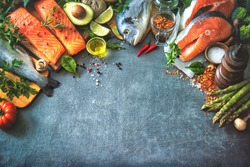 Assortment of fresh fish with aromatic herbs, spices and vegetables. Balanced diet or cooking concept