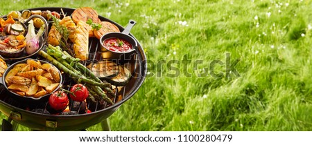 Assortment of fresh healthy vegetables on a BBQ grilling over a hot fire in a green grassy spring or summer field in banner format with copy space #1100280479
