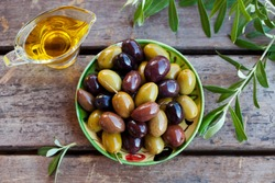 Assortment of fresh olives on a plate with olive tree brunches. Wooden background. Top view.