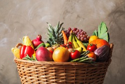 Assortment of fresh organic fruits and vegetables in basket on grey background, closeup