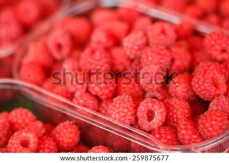 Assortment Of Fresh Organic Red Berries Raspberries At Produce Local Market In Baskets, Containers.