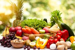 Assortment of Fresh vegetables and fruits With vitamins c from bananas, kiwi, grapes, raspberries, blueberries, and blackberries, good for the body and diet food on the table in nature background.