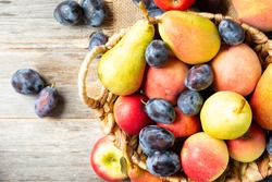 Assortment of fruits in a basket on the table. There are a lot of different raw fruits in the basket. Plums, peaches, apples and pears on the table. Healthy diet. Top view with space for text