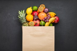 Assortment of fruits in a paper bag on black concrete. concept of vitamins in human diet.