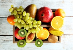 Assortment of fruits in box on wooden table