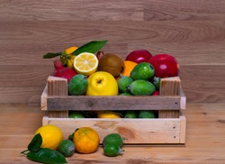 Assortment of fruits in wooden box, on wooden background. The concept of healthy food. lemon, grapes, kiwi and quince and feijoa