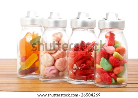 Assortment of glass jars with marshmallows, candies and red licorice on wooden background. Shallow depth of field