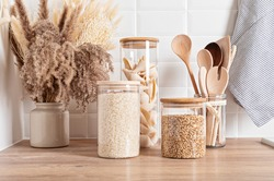 Assortment of grains, cereals and pasta in glass jars and kitchen utensils on wooden table