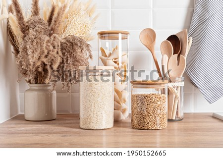 Assortment of grains, cereals and pasta in glass jars and kitchen utensils on wooden table Zdjęcia stock ©