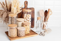 Assortment of grains, cereals and pasta in glass jars and kitchen utensils on wooden table. Healthy balanced food, sustainable lifestyle, zero waste storage, eco friendly idea