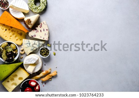 Assortment of hard, semi-soft and soft cheeses with olives, grissini bread sticks, capers, grape, on grey concrete backgound. Top view, copy space, flat lay. Cheese selection appetizer plate