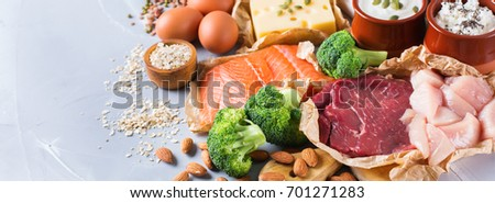 Assortment of healthy protein source and body building food. Meat beef salmon chicken breast eggs dairy products cheese yogurt beans artichokes broccoli nuts oat meal. Copy space background