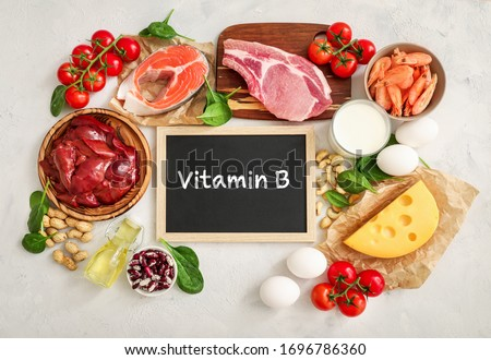 Assortment of high vitamin B sources on white background: milk, liver, olive oil, tomatoes, prawns, peanuts, beef, spinach, salmon, keshew, cheese, eggs, haricot. Top view.