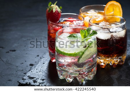 assortment of iced fruit drinks on a dark background, horizontal #422245540