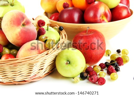 Assortment of juicy fruits in wicker basket and wooden bowl, isolated on white