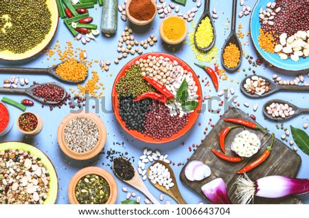 Assortment of legumes bowls and various spices  top view - Healthy food background flat lay of colorful kitchen table with beans and seeds from around the world - Concept of alternative protein diet