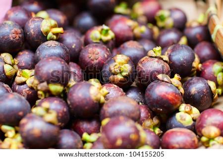 Assortment of mangosteen fruits at market stall