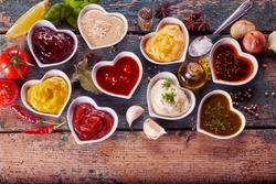 Assortment of marinades, sauces and dressings in individual heart shaped bowls surrounded by scattered spices, herbs and condiments on rustic wood