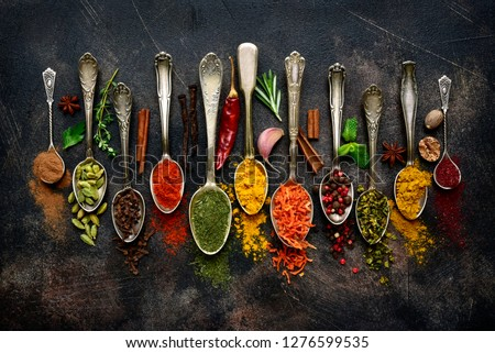 Assortment of natural spices on a vintage spoons over dark slate, stone, concrete or metal background.Top view with copy space.