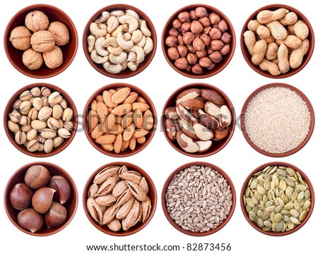 assortment of nuts and seeds in ceramic bowls isolated on white background