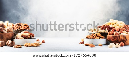 Assortment of nuts in bowls. Cashews, hazelnuts, walnuts, pistachios, pecans, pine nuts, peanuts, macadamia, almonds, brazil nuts. Food mix on gray background, copy space banner