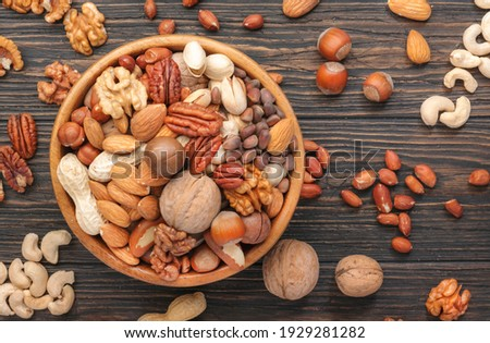 Assortment of nuts in bowls. Cashews, hazelnuts, walnuts, pistachios, pecans, pine nuts, peanuts, macadamia, almonds, brazil nuts. Food mix on wooden background, top view, copy space