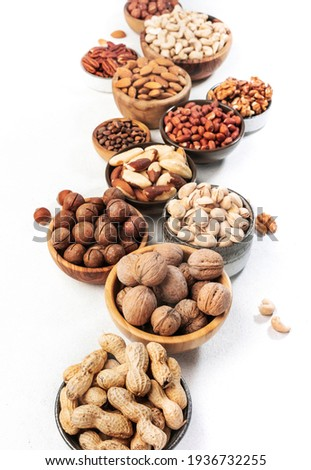 Assortment of nuts in bowls. Cashews, hazelnuts, walnuts, pistachios, pecans, pine nuts, peanuts, macadamia, almonds, brazil nuts. Food mix on white background, top view, copy space