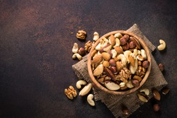 Assortment of nuts in wooden bowl on dark stone table. Cashew, hazelnuts, walnuts, almonds, brazilian nuts and pine nuts. Top view with copy space.