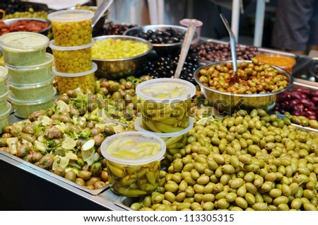 assortment of olives, pickles and salads on market stand