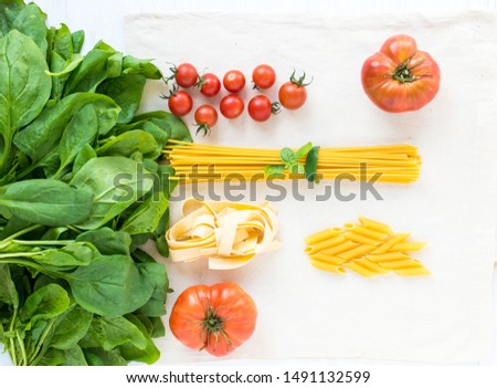 Assortment of pasta and different varieties of tomato with a bunch of spinach. Top view on a flat surface and ingredients