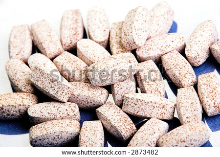 Assortment of pills over a reflective white background 2