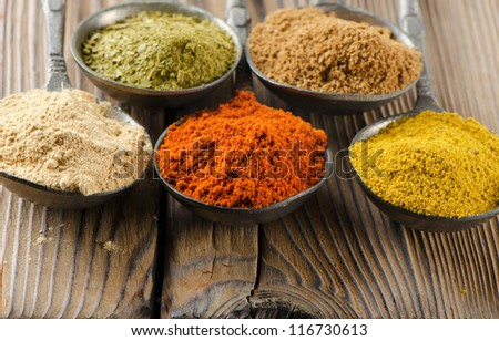 Assortment of powder spices on a wooden table