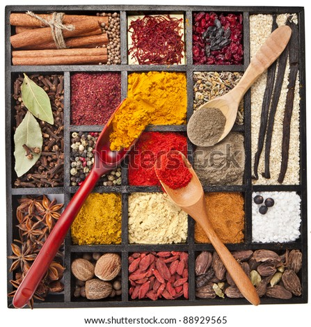 Assortment of powder spices on spoons in wooden box isolated on a white background