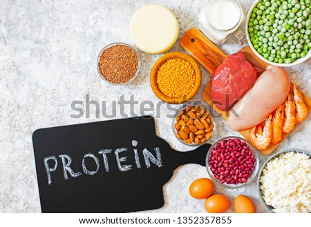 Assortment of Products with high level of protein. Healthy Protein Source. Foods for muscles building. Meat, seafood, cheese, milk, nuts, legumes, seeds, eggs, vegetables. Light background. Top view