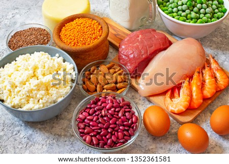 Assortment of Products with high level of protein. Healthy Protein Source. Foods for muscles building. Meat, seafood, cheese, milk, nuts, legumes, seeds, eggs, vegetables. Light background. Close-up