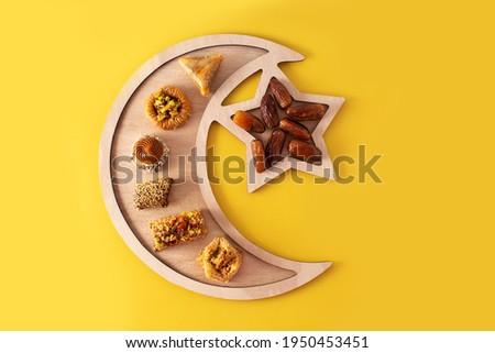 Assortment of Ramadan dessert baklava on yellow background