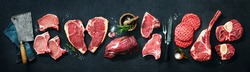 Assortment of raw cuts of meat, dry aged beef steaks and hamburger patties for grilling with seasoning and utensils on dark rustic board