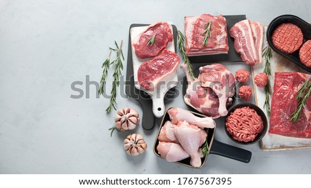 Assortment of raw meats on grey background. Top view with copy space Foto stock ©