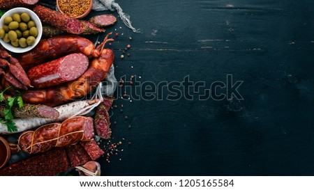 Assortment of salami and snacks. Sausage Fouet, sausages, salami, paperoni. On a black wooden background. Top view. Free space for your text.