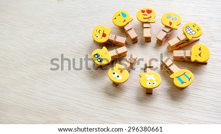 Assortment of smiley faces emoticon on clothes peg on wooden surface. Concept of emotions or meta communicative pictorial representation of a facial expression. Slightly de-focused. Copy space. #296380661