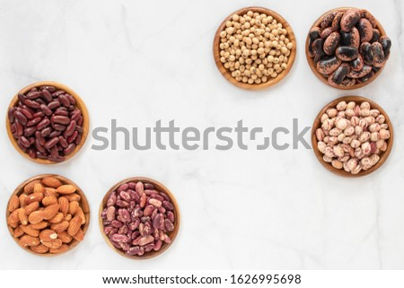 Assortment of soybean, red kidney bean, black bean, red bean and brown, pinto beans in wooden bowl on marble table.Variety beans with copy space for your text