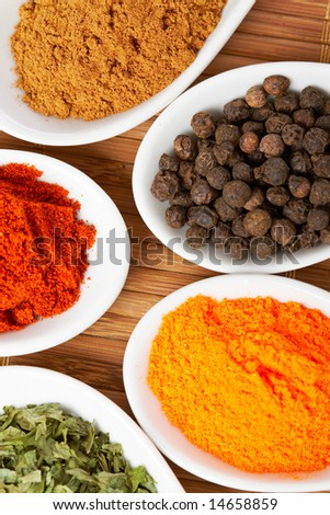 Assortment of spices in the spoons for prepare tasty food with soft shadow in the wooden background