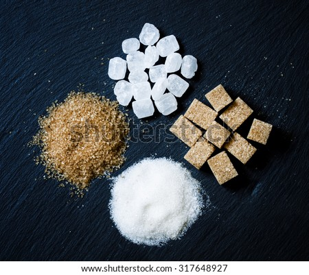 Assortment of sugar: white sand, candy sugar, brown sugar into pieces and brown sugar on a dark background, top view